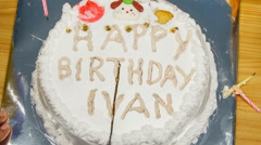 Closeup view of round white birthday cake with figures candles Stock Footage