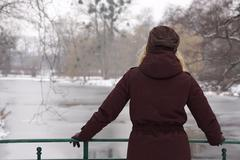 woman looking at frozen river - stock photo