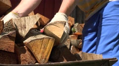 Male worker hands with gloves unload chopped wood firewood from cart. 4K Stock Footage