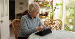 A senior woman using a digital tablet at home. Shot on RED Epic. Stock Footage