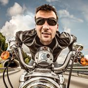 Funny Biker in sunglasses and leather jacket racing on mountain serpentine. Stock Photos