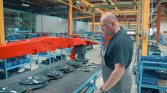 Young worker is working in a factory for agricultural machinery parts Stock Footage