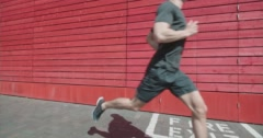 Runner jogging past red wall and 'Fire Exit' sign. Stock Footage