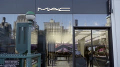 Mac cosmetics store front with sign glass window reflection next to subway NYC Stock Footage