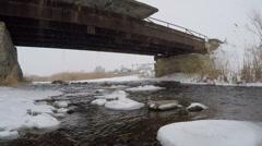 Winter river flowing under the bridge. Stock Footage