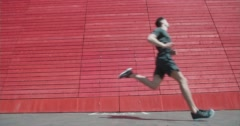 Powerful long limber runner jogging past wall. Stock Footage