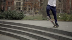 White kid ollieing down staircase in Washington Square Park in slow motion, NYC Stock Footage