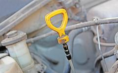 The oil dipstick of a car engine - stock photo