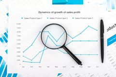 Financial chart with a magnifying glass. Report on sales for current year Stock Photos