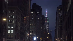 Empire State Building colorful evening lights at night tilting down to Lower 5th Stock Footage