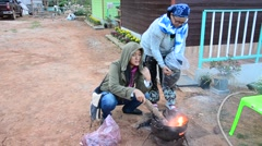 Thai woman and old women Burning sweet potato on old stove Stock Footage