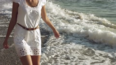 Free girl standing on the seashore washed by waves Stock Footage