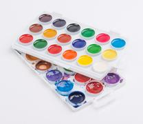 New and used watercolor paints in palette isolated on white background - stock photo