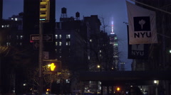 NYU flags on Samuel Rubin dorm on 5th Ave with Empire State Building night NYC - stock footage