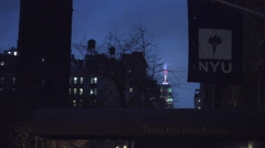 Zooming out from Empire State Building at night to NYU dorm with flags, church Stock Footage