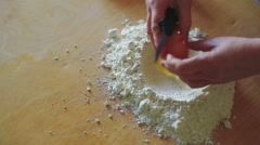 Hand to breaking an egg in flour,salt, and  mixing flour and egg on table Stock Footage
