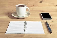 Still life photo of smartphone, notebook, coffee and pencil on wooden table. - stock photo