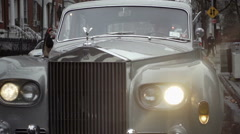Rolls-Royce grill up close moving up to 5th Ave sign on Lower Fifth Avenue NYC - stock footage