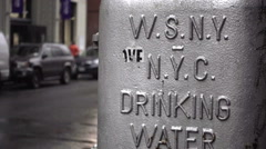 W.S.N.Y. NYC Drinking Water sign with car driving by in background outside NYU Stock Footage