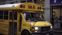 Yellow school bus driving past in slow motion NYU building Greenwich Village NYC Stock Footage