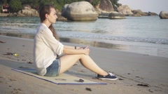 Girl Sitting on a Beach Mat near the Sea Receives a Message on Her Smartphone Stock Footage