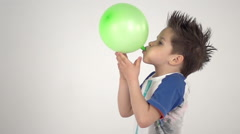 Child blowing up green balloon that flies away in slow motion Stock Footage