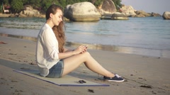 Girl Sitting on a Beach Mat near the Sea Using Smartphone Stock Footage