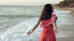 Buoyant young woman in dress walking along the seashore Stock Footage