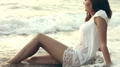 Sexy young woman in wet clothes lying on the seashore Stock Footage
