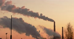 Smoke from factory chimneys over grey sky and clouds. Industrial pollution.  Arkistovideo