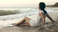 Seductive wet girl lies on the coast of the beach Stock Footage