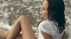 Young wet woman lies in waves on the seashore Stock Footage