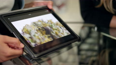 Close up of associate at marijuana shop pointing to product on a tablet Stock Footage
