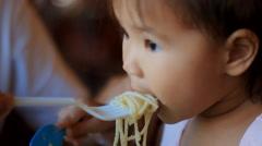 Little girl eats pasta carbonara Stock Footage