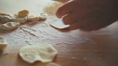 Making of dumplings. A woman is rolling dough with a rolling pin on a table - stock footage