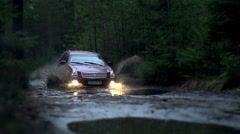 Jeep overcoming puddles and splashing mud in a forest in slow motion Stock Footage