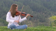 Young woman playing violin outdoors - stock footage