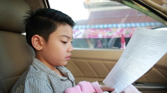 Little asian boy reading text in car Stock Footage