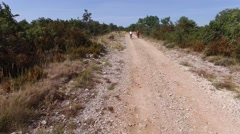 Two cyclists riding on a rural track in the garrigue or scrubland in the South - stock footage