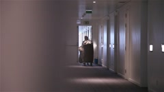 Cleaning woman pushing car in a hotel corridor, slider shot Stock Footage