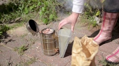 Female beekeeper lights a smoker. Stock Footage