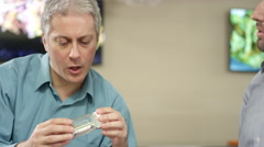 Older customer at marijuana shop looking closely at product Stock Footage