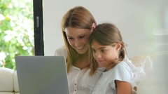 Woman with young girl using laptop computer - stock footage