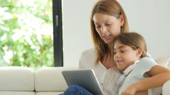 Mother and daughter websurfing on digital tablet - stock footage