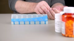 Elderly man sorting pills into daily pill box. - stock footage