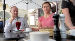 Waitress brings food to happy couple at outdoor European cafe. Stock Footage