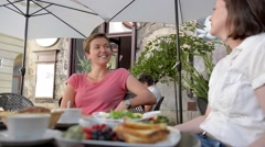 Two happy female friends at an outdoor European cafe. - stock footage
