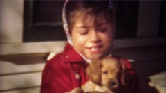 1948: Cute girl bundled up for fall plays with golden retriever puppy. GREELEY, Stock Footage