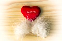 Valentine heart with white feather on a light wood - stock photo