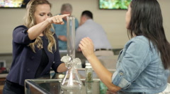 Associate at marijuana shop showing an older customer how to use a bong Stock Footage